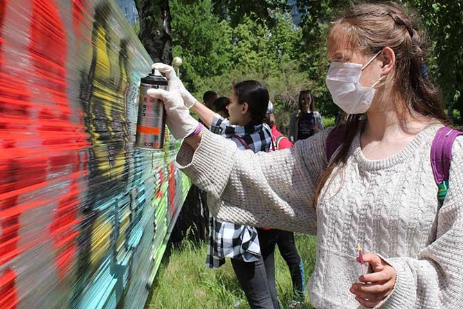 девушка расписывает объект аэрозольными красками