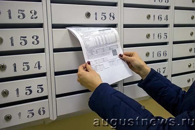 женщина достает счет за квартиру из почтового ящика