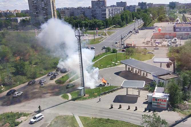 мужчина тушит огонь на автомобиле