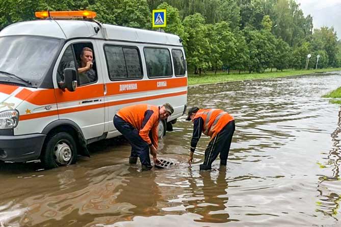 рабочие дорожной службы чистят ливневый колодец