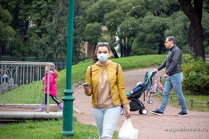 девушка идет в маске по парку
