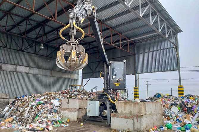 механическая рука загружает отходы на конвейер