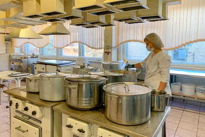 повар на кухне в школьной столовой